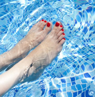 Woman's feet with painted toe nails in swimming pool