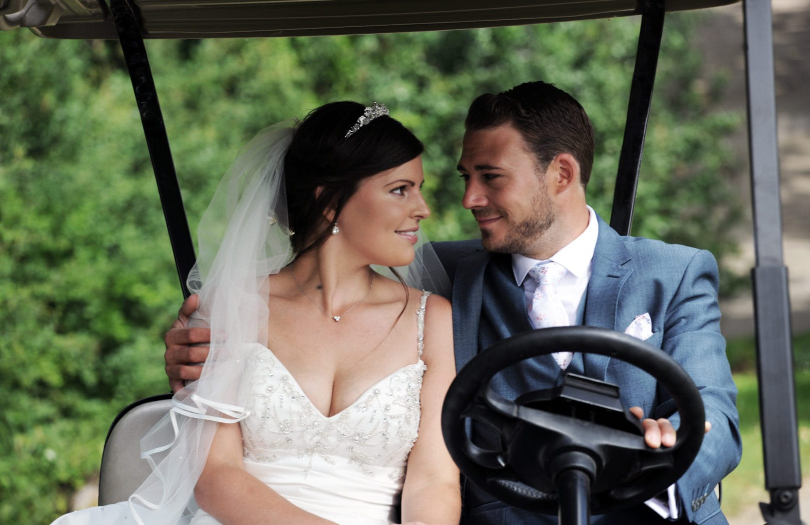 Newly wed couple in golf buggy
