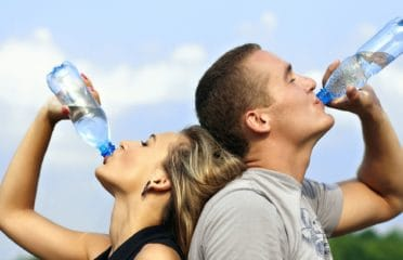 Couple drinking water from bottles