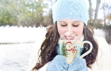 Woman in snow with mug